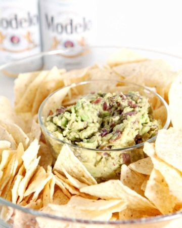 A bowl of guacamole surrounded by chips