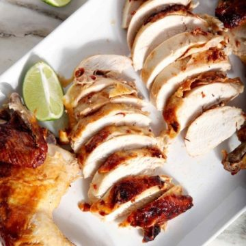 A platter of Chipotle Lime Spicy Beer Can Chicken is sliced and served on a white background with lime wedges