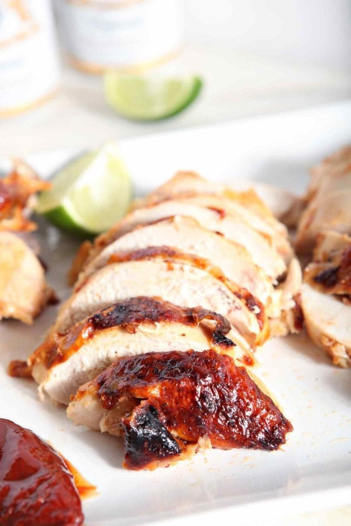 Sliced Chipotle Lime Spicy Beer Can Chicken sits on a white platter with lime wedges, ready to be plated and eaten