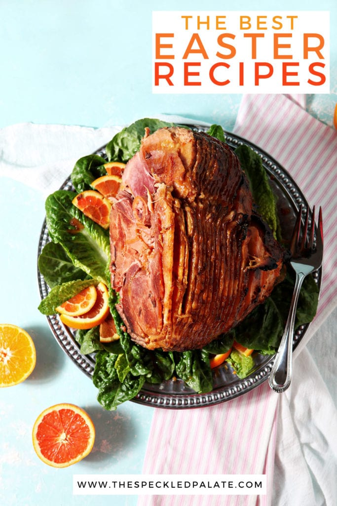 A roasted ham with sliced citrus on a turquoise surface with the text 'the best easter recipes'