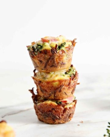 Three Gluten Free Broccoli Quiche Lorraine Bites are stacked on a marble surface before serving