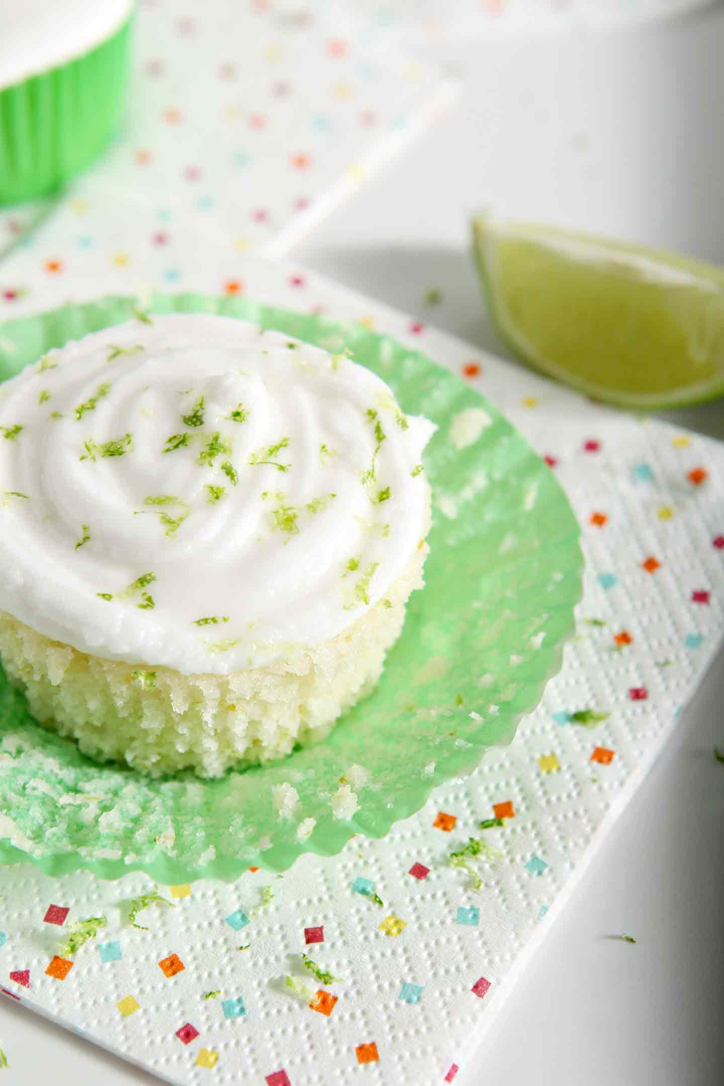 The cupcake liner of a lime cupcake is folded down. The final cupcake is sprinkled with margarita frosting and lime zest