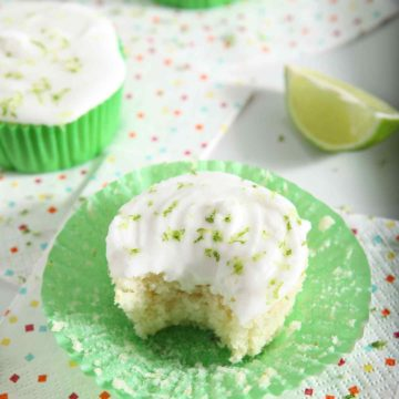 A Margarita Cupcake with Salted Tequila Frosting has a bite taken out of it, while sitting on a platter with other cupcakes on confetti napkins, before serving