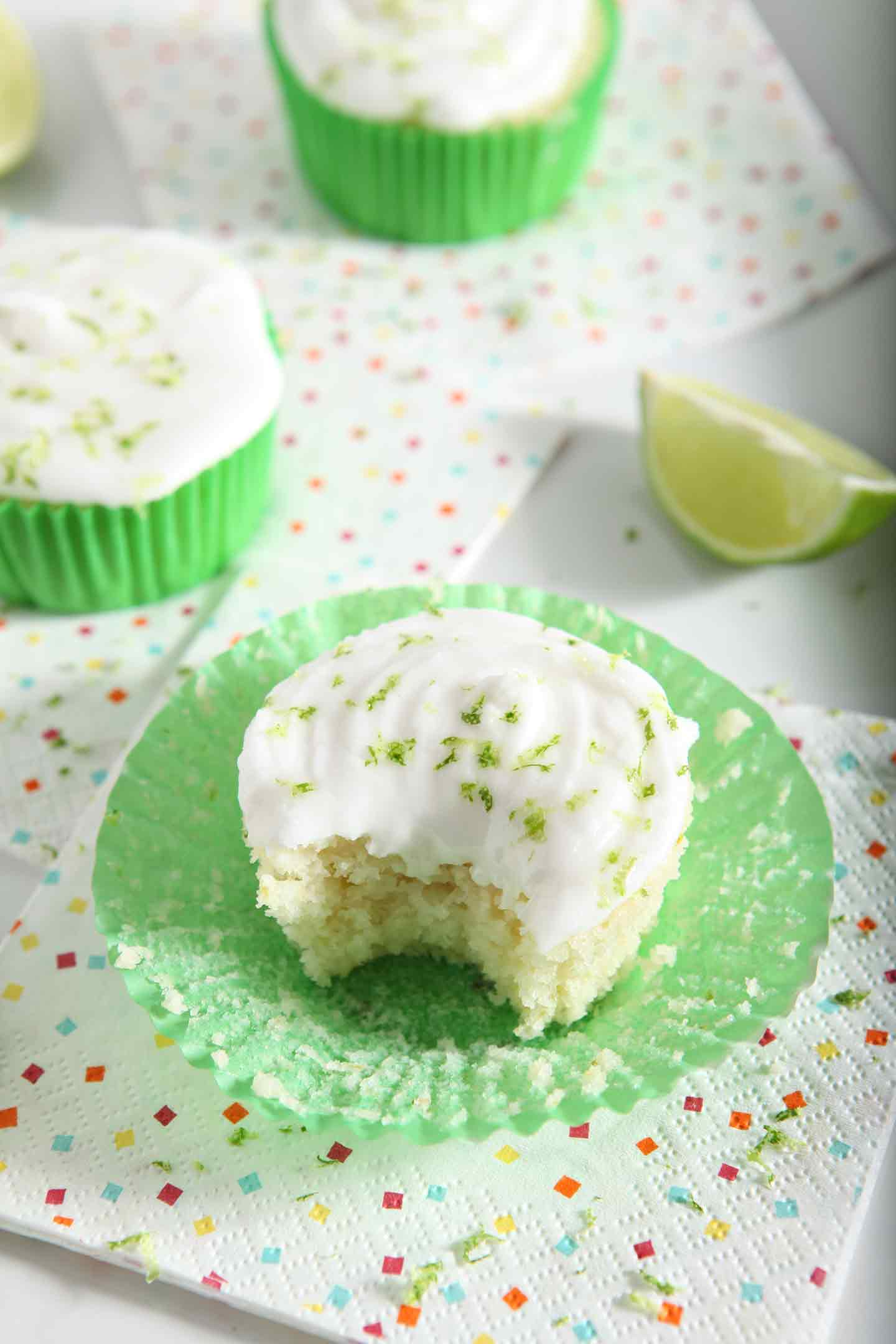 A bite is taken out of a dairy free cupcake, topped with boozy margarita frosting