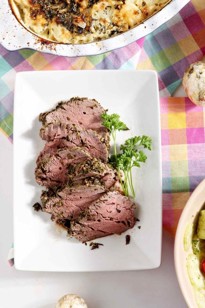Sliced pieces of Mediterranean Herb Crusted Beef Tenderloin are served on a white platter