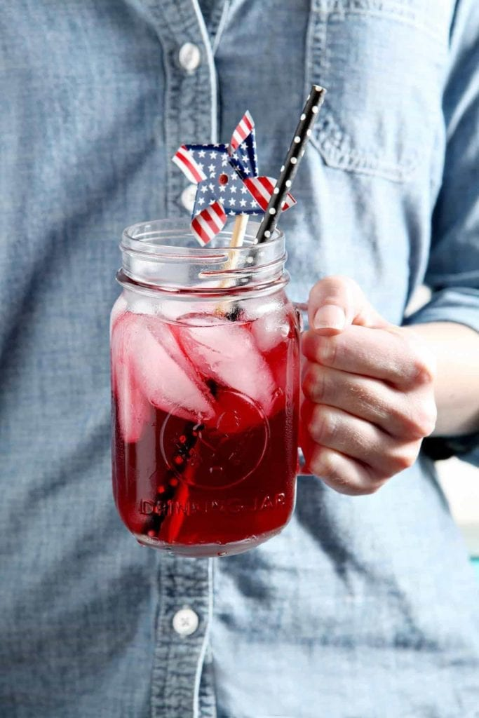 A woman holds a glass of Blackberry Tea, decorated with a patriotic pinwheel.