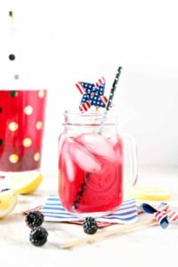 An ice cold glass of Blackberry Ginger Lemon Whole30 Tea sits on a marble counter with a pitcher of the tea behind it, surrounded by lemon slices and fresh blackberries.