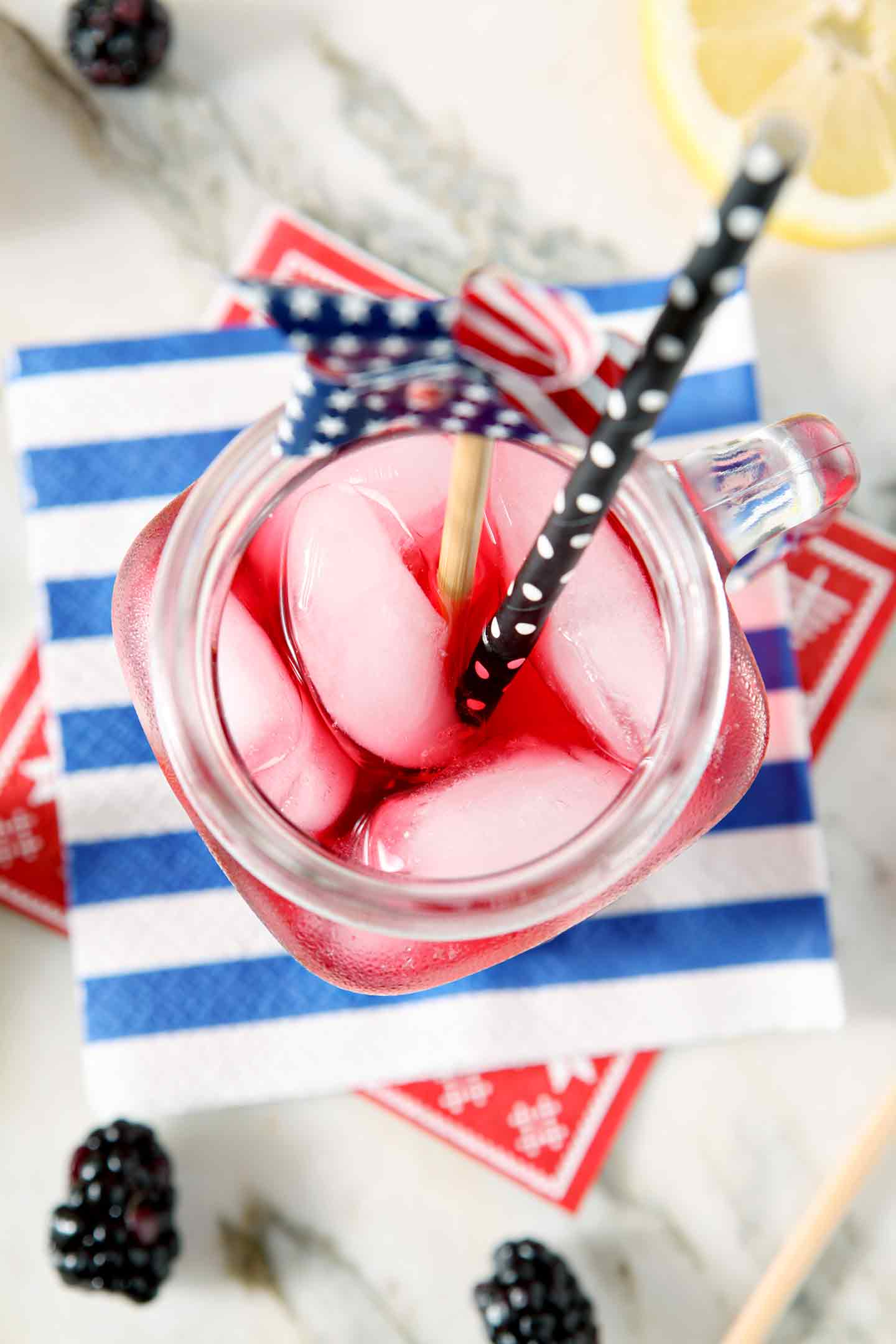 Close up of a mason jar holding Blackberry Tea with a patriotic garnish