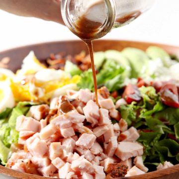 Homemade vinaigrette is drizzled onto a Cajun Cobb Salad before tossing.