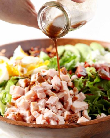 pouring dressing on a cajun cobb salad