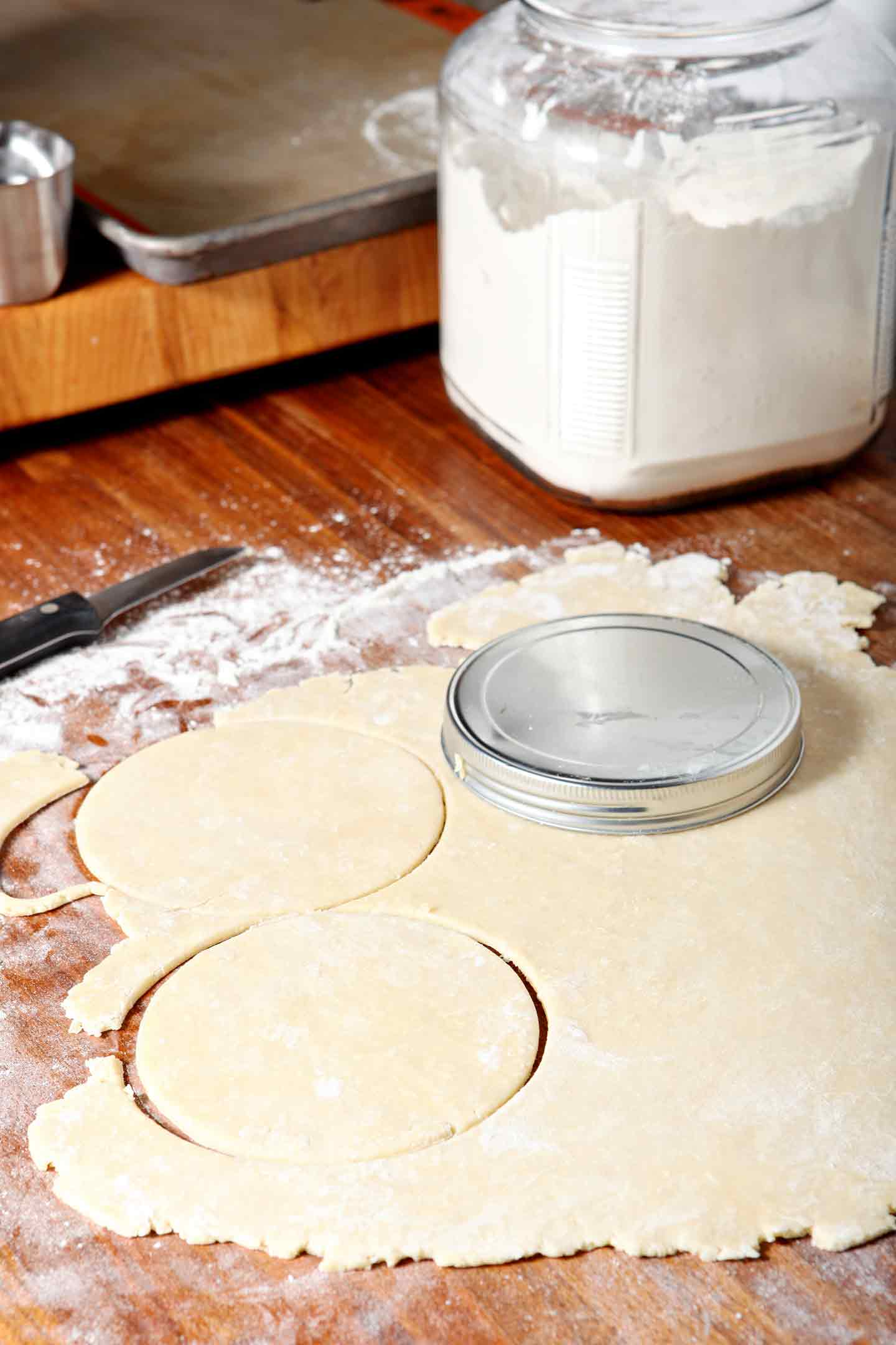A canister lid is used to form the hand pie crust for Chocolate Bourbon Pecan Hand Pies before filling.
