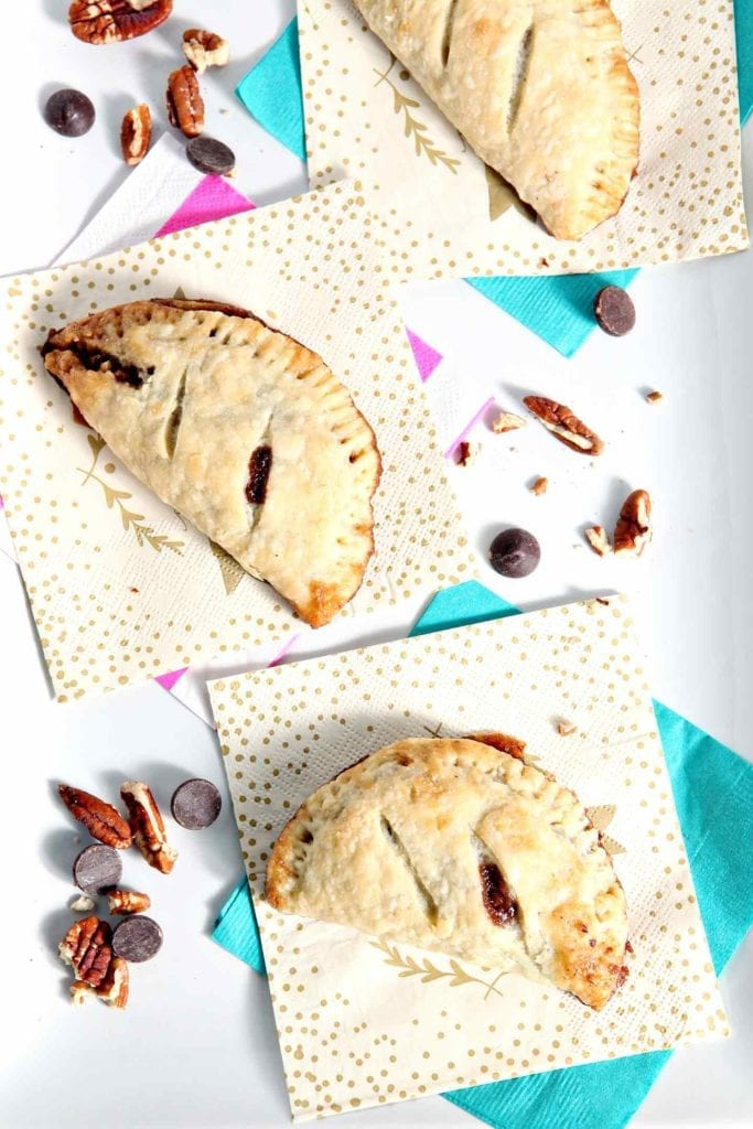 Three Chocolate Bourbon Pecan Hand Pies sit on a white platter before serving
