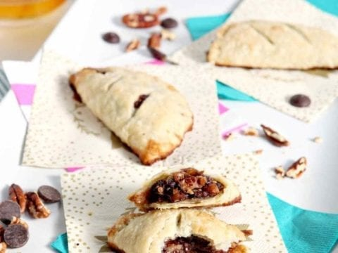 A Chocolate Bourbon Pecan Hand Pie is sliced in half and sits with two other hand pies on a white platter before serving