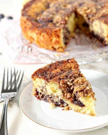 A slice of Lemon Blueberry Coffee Cake sits on a small white plate with the entire cake in the background, along with forks.