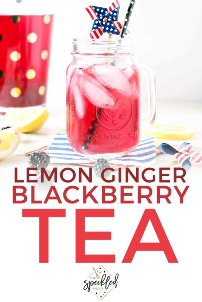 A mason jar holds a serving of blackberry tea with ice cubes and a patriotic pinwheel garnish with the text 'lemon ginger blackberry tea'