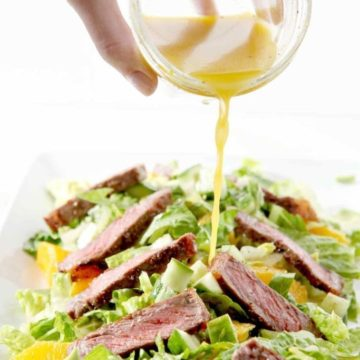 An orange vinaigrette is drizzled onto a Whole30 and paleo-friendly Orange Steak Salad.