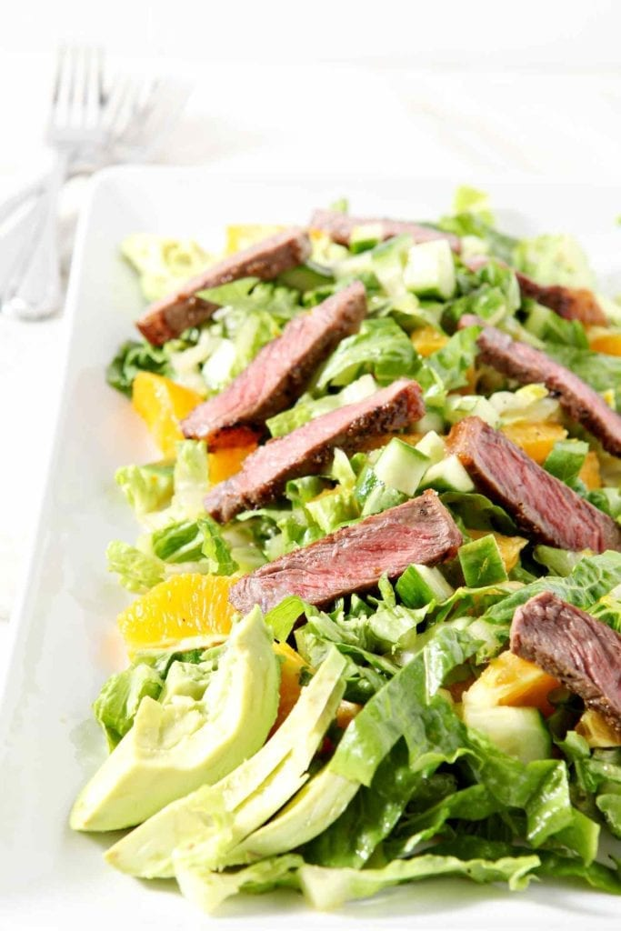 A colorful serving of Orange Steak Salad sits on a white platter before serving.