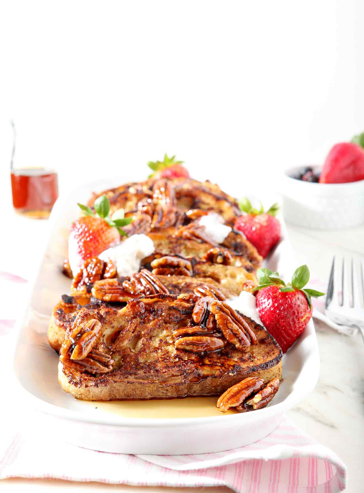Praline French Toast is served on a platter with coconut cream and fresh strawberries