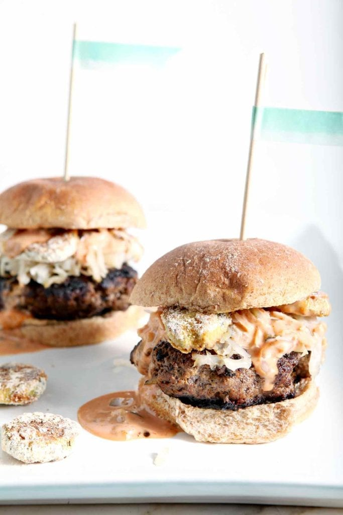 Two Sauerkraut Burgers with Oven Fried Pickles and Sweet Sriracha Sauce are shown on a platter, ready for eating