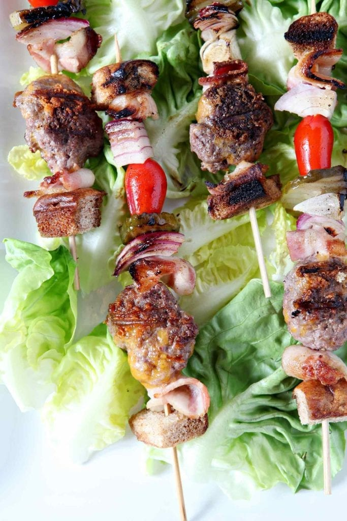 Close up of cooked deconstructed burger bites on skewers, laid out on lettuce