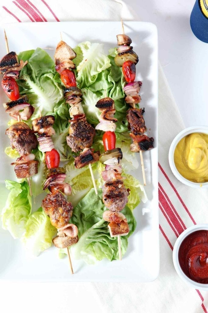 Overhead image of several Cheeseburger Kebabs, laid out on top of lettuce on a white platter, served with ketchup and mustard