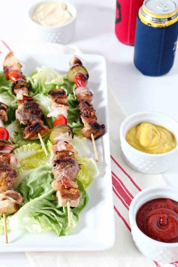 Cheeseburger kebabs are served on a white platter on top of lettuce