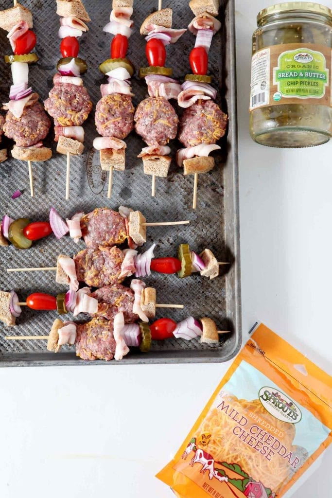 Prepared burger bites on kebab skewers are laid out on a baking sheet, surrounded by Sprouts ingredients