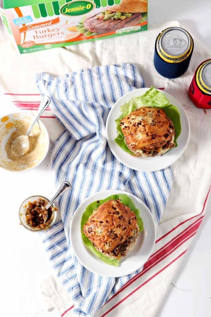 Two Louisiana Cajun Turkey Burgers with Étouffée Relish and Creamy Cajun Sauce are served on a white background with all the fixings