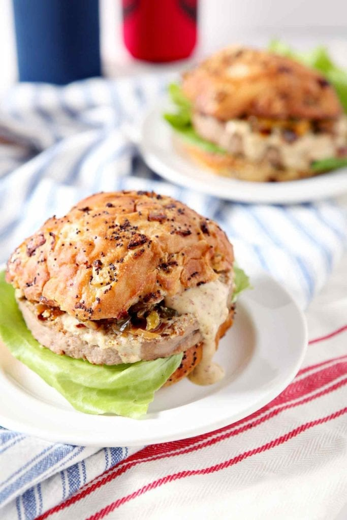 Two Louisiana Cajun Turkey Burgers with Étouffée Relish and Creamy Cajun Sauce served on white plates with red, white and blue napkins on a white background