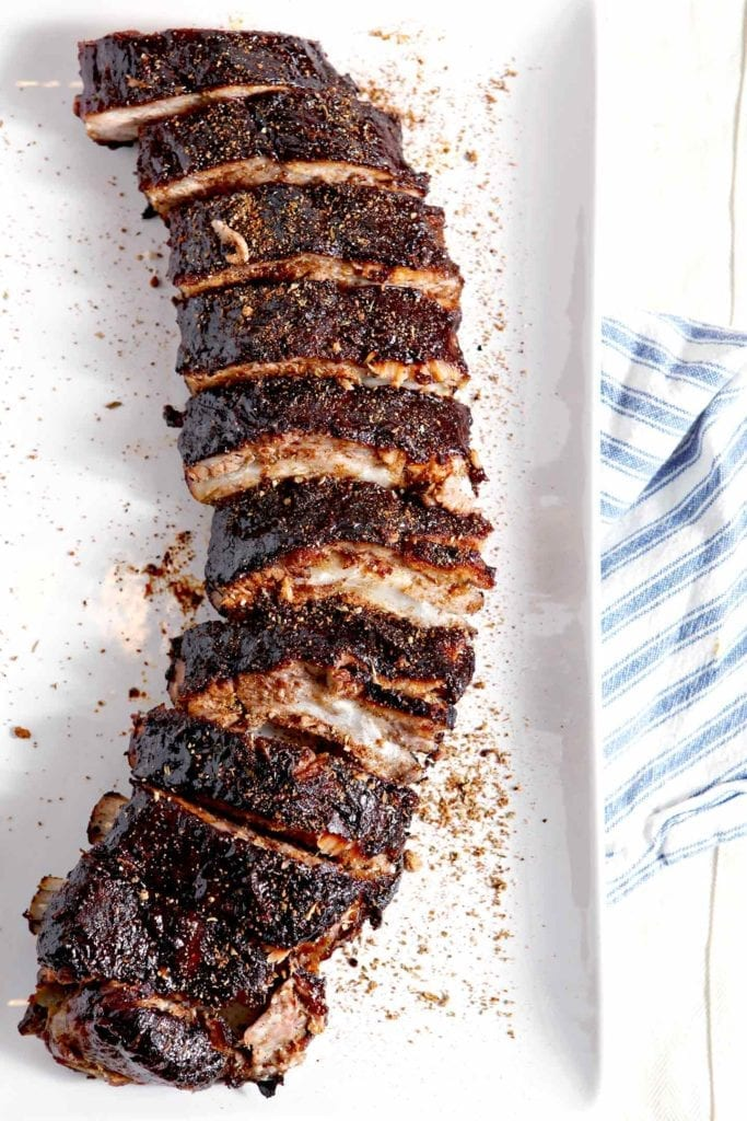 Sliced and seasoned Memphis-Style Barbecue Ribs on a white platter, set on top of a blue and white striped towel before serving
