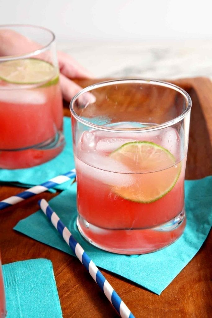 Close up of two glasses of Spiked Watermelon Limeade on a wooden tray