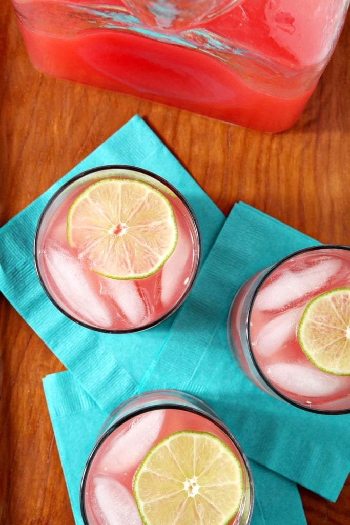 Overhead of three watermelon cocktails garnished with lime rounds