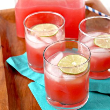 Three glasses of Spiked Watermelon Limeade are served on a platter with a pitcher