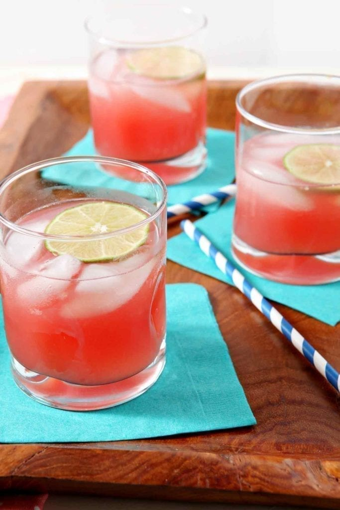 Three glasses of Spiked Watermelon Limeade are served on a wooden platter.