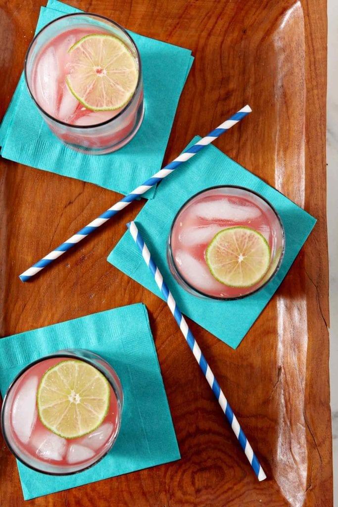 Overhead of two watermelon limeade vodka drinks
