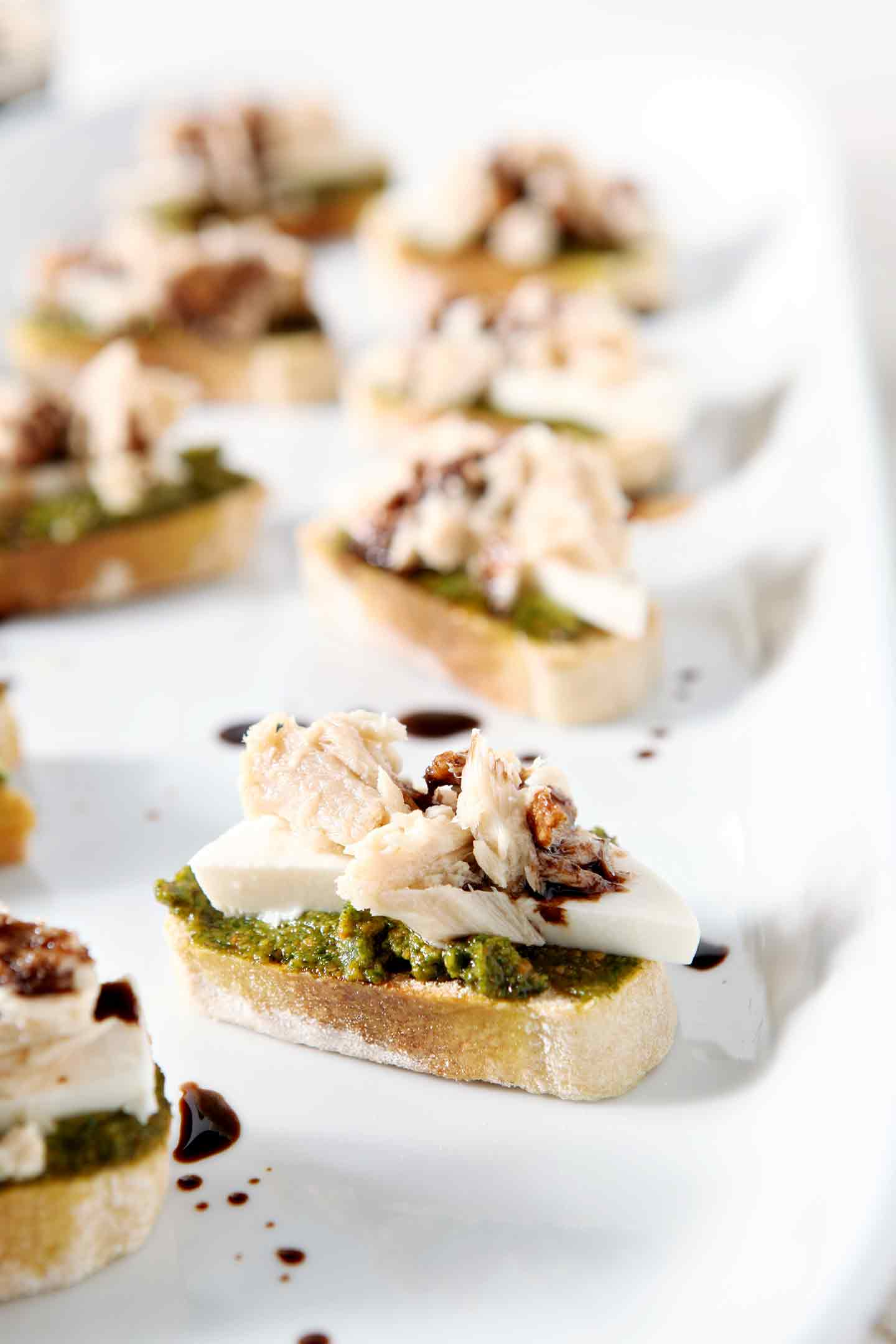 Wow party guests and your own tastebuds with bite-sized Tuna Pesto Crostini! This appetizer, an adaptation on a favorite Italian sandwich, is scrumptious. #recipe #appetizer