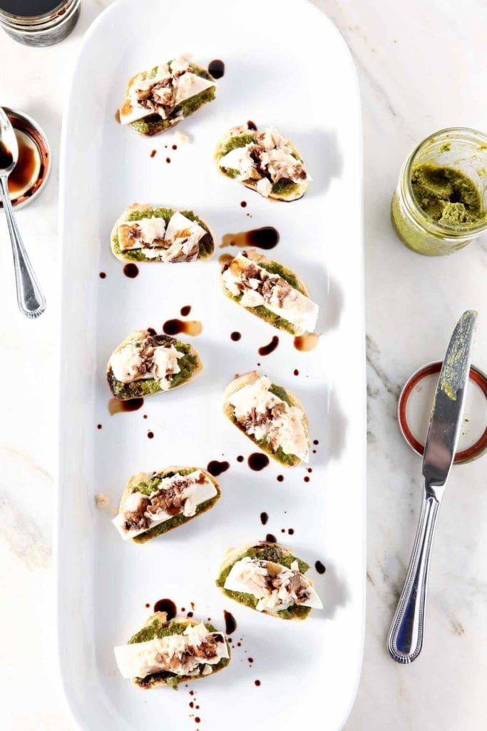 Overhead image of Tuna Pesto Crostini, served on a white platter, on a white marble background with the fixings.