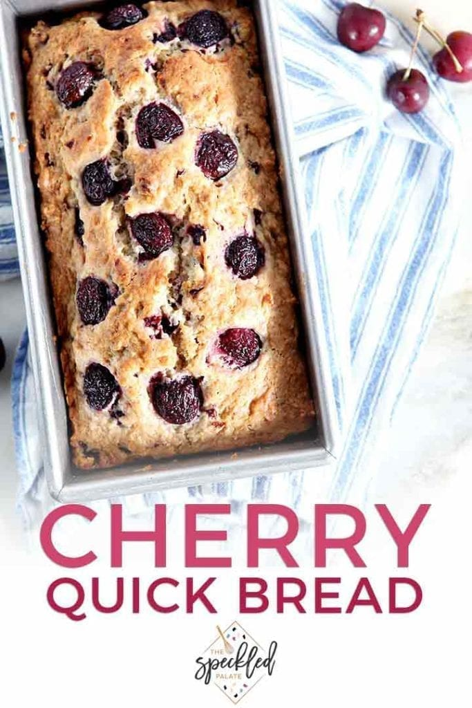 A loaf of Fresh Cherry Bread in its pan on top of a blue and white striped towel with the text 'cherry quick bread'