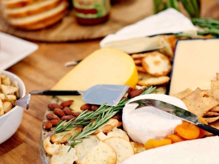 A cheese tray on a table with food at a potluck party