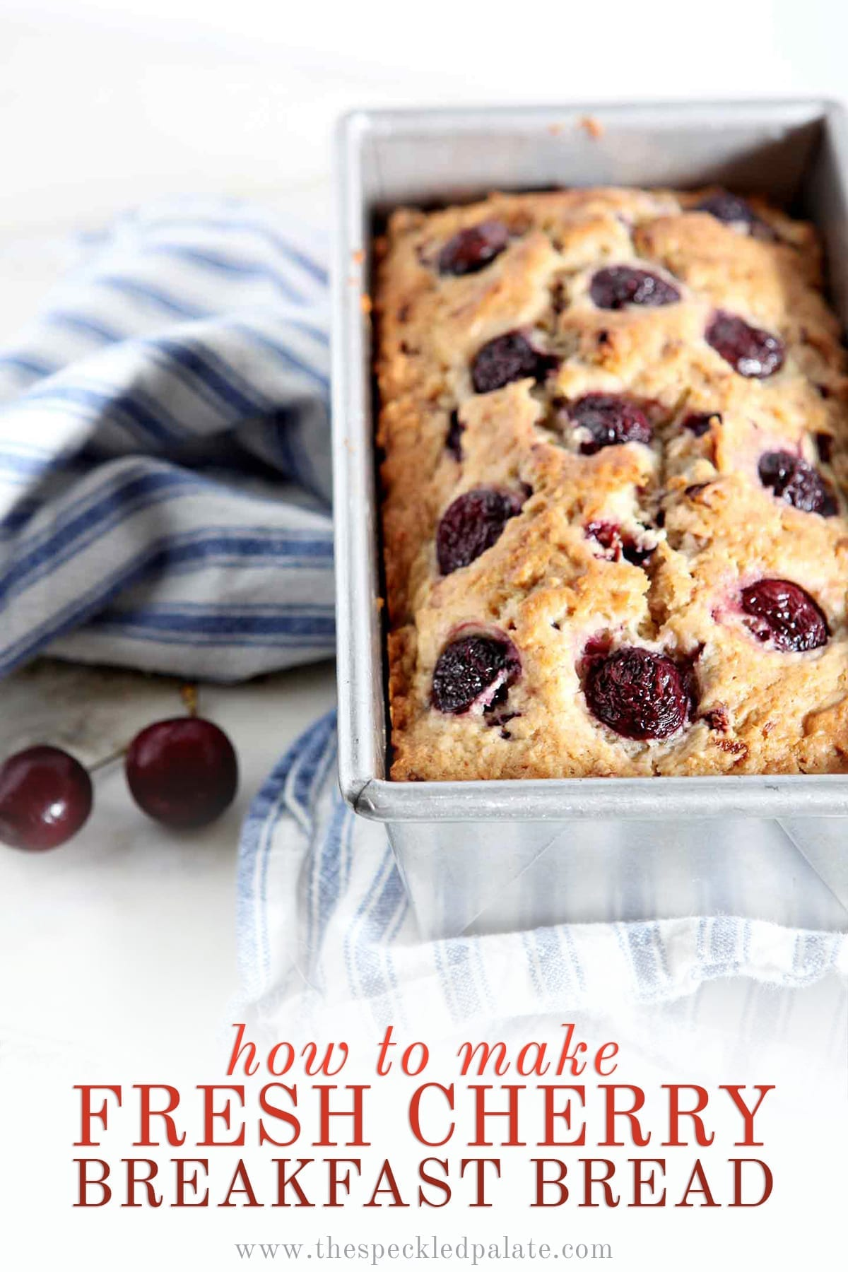 A loaf of Fresh Cherry Bread in its pan on a blue and white striped towel, next to fresh cherries with the text 'how to make fresh cherry breakfast bread'