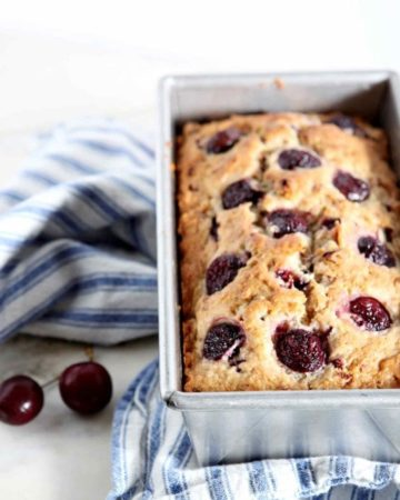 A loaf of Fresh Cherry Bread in its pan on a blue and white striped towel, next to fresh cherries