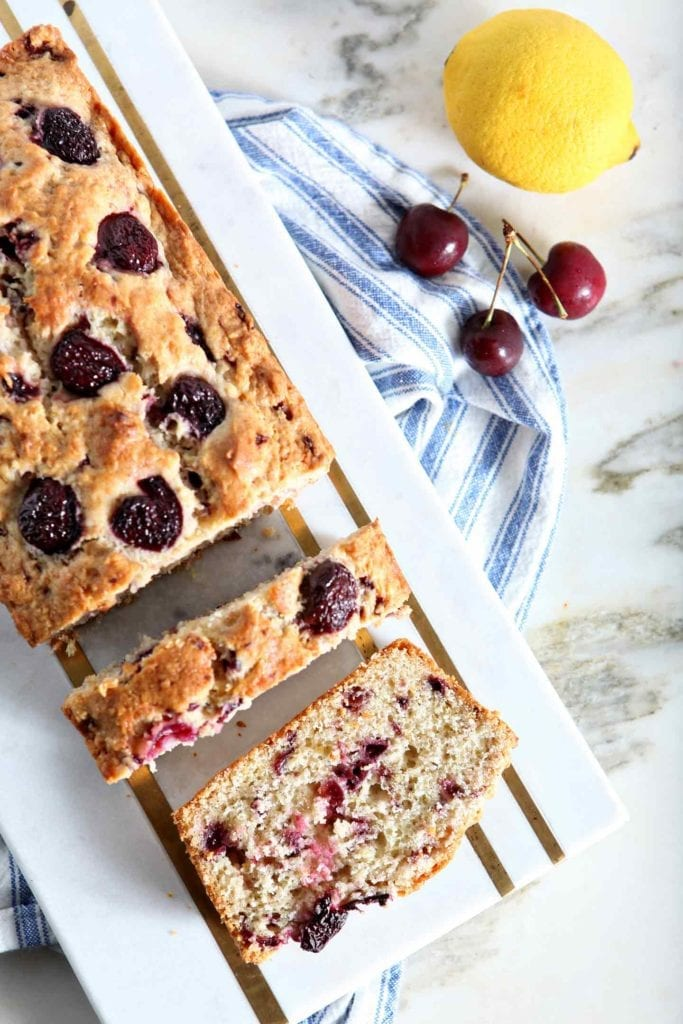 Fresh Cherry Quick Bread is sliced on a marble cutting board, surrounded by a lemon and other cherries