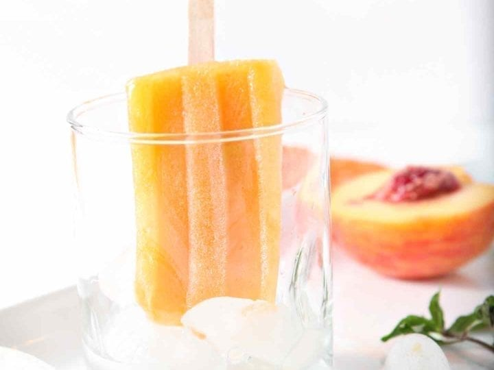 A lone Peach Julep Popsicle hangs out in a glass, surrounded by a halved peach and sprigs of mint