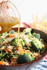 Homemade honey vinaigrette is drizzled onto Ramen Noodle and Clementine Salad.