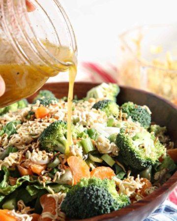 pouring dressing on ramen noodle clementine salad