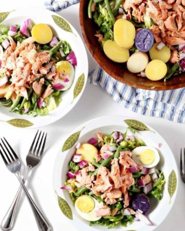 Overhead image of two Salmon Niçoise Salads, ready to be eaten