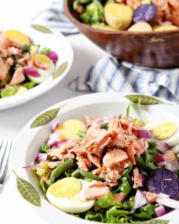 salmon nicoise salad in two white bowls with green leaves
