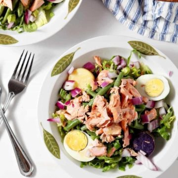 Two bowls of Salmon Niçoise Salad on a white background from above before eating