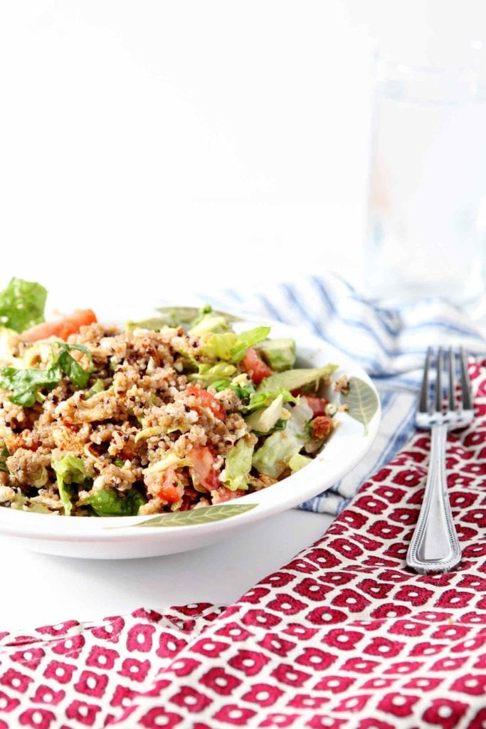 Summer Quinoa Salad in a white bowl with red and blue napkins surrounding it