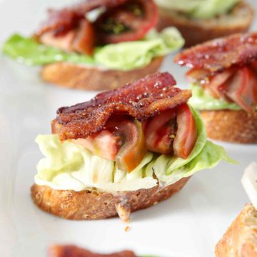 A platter of several BLT Bruschetta, laid out before a baby shower on a light pink towel